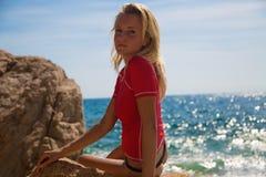 Muchacha atractiva en sportwear y tanga en la playa rocosa imagen de archivo