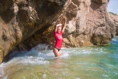 Muchacha atractiva en sportwear y tanga en la playa rocosa Fotografía de archivo libre de regalías