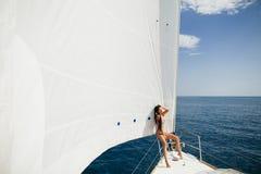 Muchacha atractiva en traje de baño en el yate debajo de la vela blanca grande Imagen de archivo libre de regalías