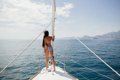 Muchacha atractiva en traje de baño en el yate en las zonas tropicales Foto de archivo