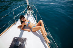 Muchacha atractiva en traje de baño en el yate en las zonas tropicales Foto de archivo libre de regalías