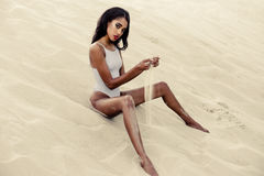 Muchacha atractiva en traje de baño en la playa Foto de archivo libre de regalías