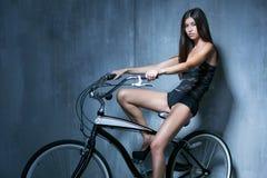 Muchacha atractiva en un chaleco negro y los pantalones cortos que se sientan en la bici en Fotos de archivo libres de regalías