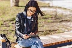 muchacha atractiva en vidrios con la tableta en el parque imágenes de archivo libres de regalías