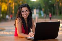 Muchacha atractiva feliz con su computadora portátil al aire libre Imagen de archivo libre de regalías