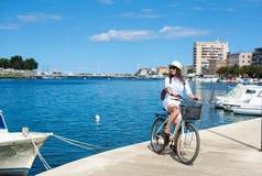Muchacha atractiva feliz en gafas de sol y con la mochila que monta una bici a lo largo de la acera pedregosa imágenes de archivo libres de regalías