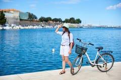 Muchacha atractiva feliz en gafas de sol y con la mochila que monta una bici a lo largo de la acera pedregosa imagen de archivo libre de regalías