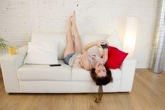 Muchacha atractiva feliz que juega en el sofá casero que toma el retrato del selfie con el teléfono móvil que se divierte Foto de archivo libre de regalías