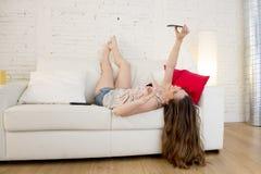 Muchacha atractiva feliz que juega en el sofá casero que toma el retrato del selfie con el teléfono móvil que se divierte Imagen de archivo