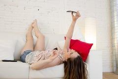 Muchacha atractiva feliz que juega en el sofá casero que toma el retrato del selfie con el teléfono móvil que se divierte Fotografía de archivo libre de regalías