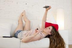 Muchacha atractiva feliz que juega en el sofá casero que toma el retrato del selfie con el teléfono móvil que se divierte Fotografía de archivo