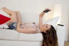 Muchacha atractiva feliz que juega en el sofá casero que toma el retrato del selfie con el teléfono móvil que se divierte Imágenes de archivo libres de regalías