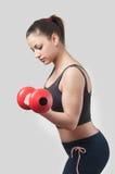 Muchacha atractiva fuerte con pesa de gimnasia Fotografía de archivo libre de regalías
