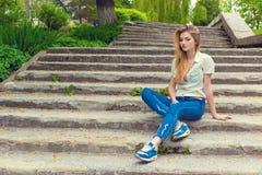 Muchacha atractiva hermosa con el pelo largo que se sienta en las escaleras tristes en vaqueros y camisa Fotos de archivo
