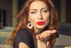 Muchacha atractiva hermosa con el pelo rojo con los labios rojos grandes con maquillaje en la ciudad en un día de verano soleado Fotos de archivo libres de regalías