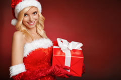 Muchacha atractiva hermosa de Papá Noel con la caja de regalo. Imagen de archivo