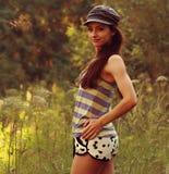 Muchacha atractiva hermosa en pantalones cortos y sombrero en parque Foto de archivo