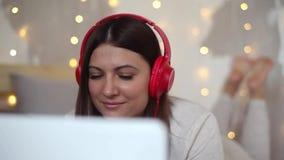 Muchacha atractiva hermosa en pijamas que escucha la música en los auriculares usando el ordenador portátil con el buen humor que almacen de metraje de vídeo