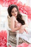 Muchacha atractiva hermosa en un vestido largo con las flores rosadas enormes que se sientan por la ventana Imagen de archivo