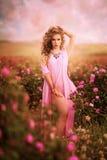 Muchacha atractiva hermosa en un vestido rosado que se coloca en las rosas del jardín Fotografía de archivo