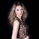 Muchacha atractiva hermosa en vestido del leopardo en maquillaje brillante en el estudio en un fondo negro Imagen de archivo libre de regalías