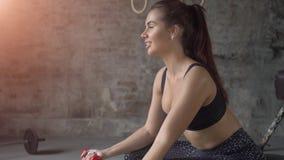 Muchacha atractiva hermosa joven en bola de la aptitud en el gimnasio con pesas de gimnasia rojas, deporte y concepto sano de la  almacen de metraje de vídeo