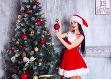 Muchacha atractiva hermosa que desgasta la ropa de Papá Noel Mujer joven que adorna el árbol de navidad con las bolas rojas en ca Fotografía de archivo
