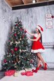 Muchacha atractiva hermosa que desgasta la ropa de Papá Noel Mujer joven que adorna el árbol de navidad con las bolas rojas en ca Foto de archivo libre de regalías