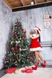 Muchacha atractiva hermosa que desgasta la ropa de Papá Noel Mujer joven que adorna el árbol de navidad con las bolas rojas en ca Fotografía de archivo libre de regalías