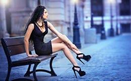 Muchacha atractiva hermosa que lleva la falda corta y los tacones altos que se colocan afuera en escena urbana imagenes de archivo