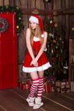 Muchacha atractiva hermosa que lleva la ropa de Papá Noel en Foto de archivo