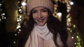 Muchacha atractiva hermosa que se coloca cerca de una ventana-tienda adornada con las guirnaldas, llevando un sombrero y y mirand almacen de metraje de vídeo