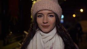 Muchacha atractiva hermosa que se coloca cerca de una ventana-tienda adornada con las guirnaldas y y que mira en la cámara Año Nu metrajes