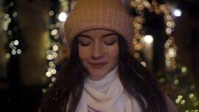 Muchacha atractiva hermosa que se coloca cerca de una ventana-tienda adornada con las guirnaldas y y que mira en la cámara Año Nu almacen de video