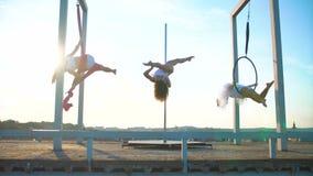 Muchacha atractiva hermosa tres que realiza trucos acrobáticos en el tejado en la puesta del sol