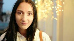 Muchacha atractiva joven cerca de las decoraciones del día de fiesta del centelleo, tono amarillo del color del vintage almacen de video