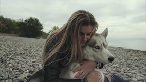 Muchacha atractiva joven con el perro del husky siberiano que se sienta en la costa almacen de metraje de vídeo