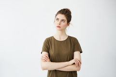 Muchacha atractiva joven con los brazos cruzados que piensa la mirada a la distancia sobre el fondo blanco Fotos de archivo
