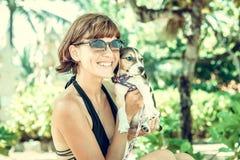Muchacha atractiva joven con su beagle del perro casero en la playa de la isla tropical Bali, Indonesia Momentos felices Fotos de archivo libres de regalías
