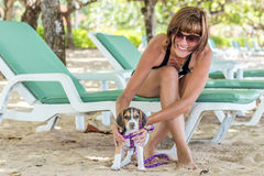Muchacha atractiva joven con su beagle del perro casero en la playa de la isla tropical Bali, Indonesia Momentos felices Imagen de archivo