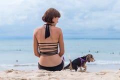 Muchacha atractiva joven con su beagle del perro casero en la playa de la isla tropical Bali, Indonesia Momentos felices Foto de archivo