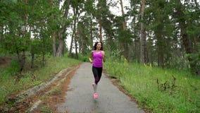 Muchacha atractiva joven, corriendo con la cámara lenta de madera almacen de metraje de vídeo