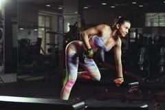 Muchacha atractiva joven de la aptitud en el gimnasio que hace ejercicios con pesas de gimnasia