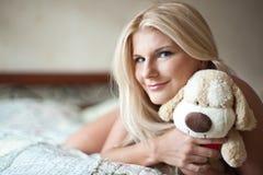 Muchacha atractiva joven del playfull en una cama con el juguete Imagen de archivo