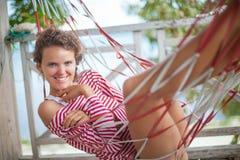 Muchacha atractiva joven del retrato que se relaja en casa de planta baja de la playa en hamaca Verano al aire libre sonriente de Imágenes de archivo libres de regalías