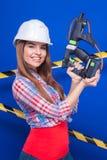 Muchacha atractiva joven del trabajador en camisa chechered, el casco blanco y la mezclilla imagen de archivo