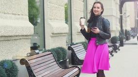 Muchacha atractiva joven en chaqueta de cuero negra y falda rosada soportes cerca de los bancos, mano que sostiene el café en una metrajes