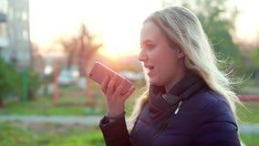 Muchacha atractiva joven en la calle, mensajero del mensaje de la voz almacen de video