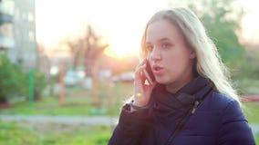Muchacha atractiva joven en la calle que habla en el teléfono almacen de metraje de vídeo