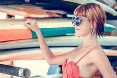 Muchacha atractiva joven en traje de baño rojo - persona que practica surf con el tablero de resaca que presenta en la playa del  Foto de archivo
